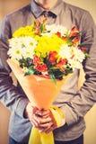 Укомплектуйте личным составом держать букет желтых и оранжевых роз День Women s, Va Стоковые Изображения RF