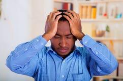 Укомплектуйте личным составом держать его голову с обеими сторонами рук, pensative и стресса Стоковые Фотографии RF