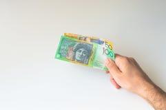 Укомплектуйте личным составом держать 100 и 50 австралийских долларов в его Стоковые Изображения