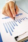 Укомплектуйте личным составом держать карандаш работая на диаграмме Стоковые Изображения RF