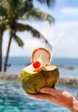 Укомплектуйте личным составом держать коктеиль кокоса с выпивая соломой и коктеиль ch Стоковое Фото