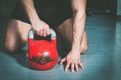 Укомплектуйте личным составом держать колокол чайника с его рукой на поле спортзала Стоковое Изображение RF