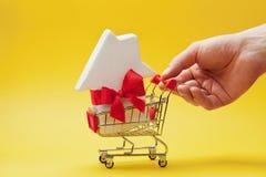 Укомплектуйте личным составом держать магазинную тележкау руки с лентой украшенной домом на желтой предпосылке Покупать новые дом стоковая фотография