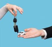 Укомплектуйте личным составом держать малый автомобиль, женщину держа ключ автомобиля Стоковая Фотография