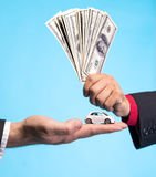 Укомплектуйте личным составом держать малый автомобиль, другой человека держа долларовые банкноты Стоковое Изображение RF
