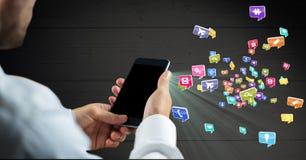 Укомплектуйте личным составом держать мобильный телефон и различные значки применения в предпосылке Стоковая Фотография RF