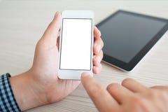 Укомплектуйте личным составом держать мобильный телефон с изолированным экраном над таблицей стоковая фотография