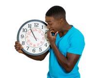 Укомплектуйте личным составом держать настенные часы, усиленные сдерживая ногти надавленные нехваткой времени стоковые изображения rf