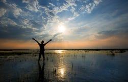 Укомплектуйте личным составом держать оружия вверх в хвалении в заходе солнца пока находящся в воде Стоковые Фотографии RF