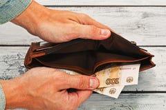 Укомплектуйте личным составом держать почти пустой бумажник с русскими деньгами Стоковая Фотография RF