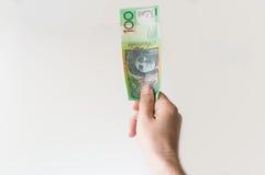 Укомплектуйте личным составом держать 100 примечаний австралийского доллара в его руке Стоковые Фото