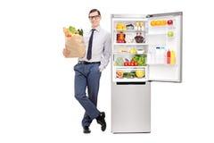 Укомплектуйте личным составом держать продуктовую сумку и полагаться на холодильнике стоковая фотография