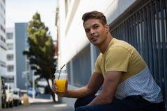 Укомплектуйте личным составом держать сок смотря отсутствующий пока сидящ стеной в городе Стоковая Фотография