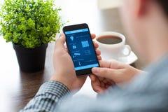 Укомплектуйте личным составом держать телефон с домом программы умным на экране стоковое фото rf