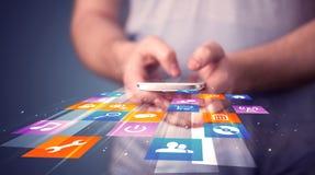 Укомплектуйте личным составом держать умный телефон с красочными значками применения Стоковое Изображение RF