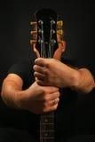 Укомплектуйте личным составом держать шею гитары при 2 руки изолированной на черноте Стоковая Фотография RF