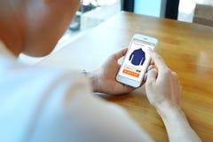 Укомплектуйте личным составом держать smartphone с выберите рубашку на вебсайте ecommerce стоковые изображения rf