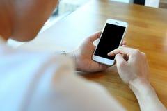 Укомплектуйте личным составом держать smartphone с выберите рубашку на вебсайте ecommerce стоковое изображение rf
