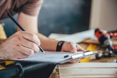 Укомплектуйте личным составом делать план проекта с карандашем на таблице Стоковое фото RF