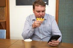 Укомплектуйте личным составом еду кофе пирога выпивая смотря телефон стоковая фотография rf