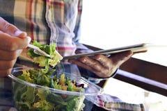 Укомплектуйте личным составом еду подготовленного салата и использование таблетки стоковое изображение