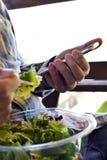 Укомплектуйте личным составом еду подготовленного салата и использование smartphone стоковое фото