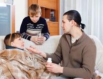 Укомплектуйте личным составом заботить для больной жены, сына помогает ему стоковая фотография rf