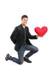 Укомплектуйте личным составом заискивать на одном колене и держать красное сердце Стоковая Фотография