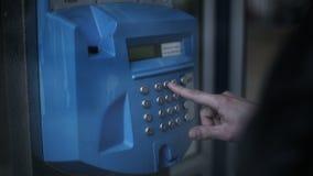 Укомплектуйте личным составом звонить телефонный звонок на общественной переговорной будке в городе сток-видео