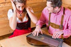 Укомплектуйте личным составом играть бедно на цитре в хате горы Стоковое Фото