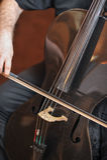 Укомплектуйте личным составом играть виолончель, поднимающее вверх руки близкое Музыкальный инструмент оркестра виолончели играя  Стоковое фото RF
