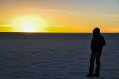 Укомплектуйте личным составом играть главные роли на заходе солнца в Саларе de Uyuni, Боливии Стоковое Фото