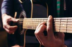 Укомплектуйте личным составом играть музыку на черной деревянной акустической гитаре Стоковая Фотография RF