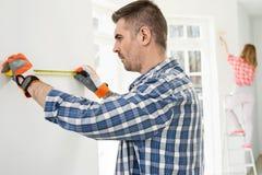Укомплектуйте личным составом измеряя стену с картиной женщины в предпосылке Стоковая Фотография RF