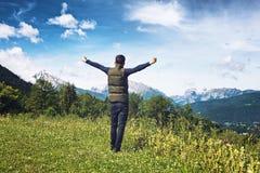 Укомплектуйте личным составом ликование на плато обозревая Альпы стоковые фото