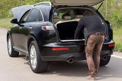 Укомплектуйте личным составом искать инструменты в ботинке его автомобиля Стоковые Фотографии RF