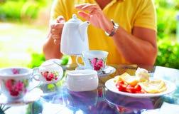 Укомплектуйте личным составом лить английский чай в чашке, на саде лета Стоковая Фотография
