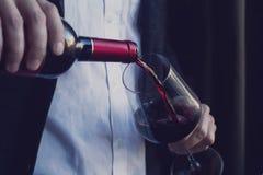 Укомплектуйте личным составом лить красное вино в стекло Стоковое фото RF