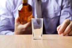 Укомплектуйте личным составом лить спирт в стекло Стоковое Фото