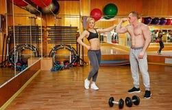 Укомплектуйте личным составом и женщина в спортзале с гантелями Стоковая Фотография RF