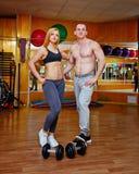 Укомплектуйте личным составом и женщина в спортзале с гантелями Стоковые Изображения