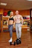 Укомплектуйте личным составом и женщина в спортзале с гантелями Стоковая Фотография