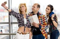 Укомплектуйте личным составом и женщина 2 держа пасспорт с билетами и картой и сфотографировал европейцы Собранный в экскурсии Стоковое Изображение