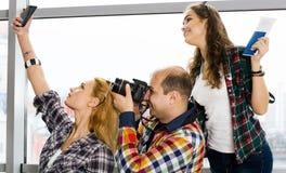 Укомплектуйте личным составом и женщина 2 держа пасспорт с билетами и картой и сфотографировал европейцы Собранный в экскурсии Стоковые Фото