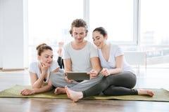 Укомплектуйте личным составом и 2 женщины используя таблетку в студии йоги совместно Стоковая Фотография