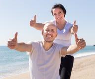 Укомплектуйте личным составом и средн-постаретая женщина в белой футболке сидя на beac Стоковое Изображение