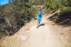 Укомплектуйте личным составом идти вдоль песочной дороги в лесе можжевельника Стоковые Фотографии RF