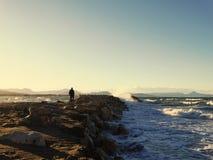 Укомплектуйте личным составом идти к морю на камнях, выплеску волны Стоковая Фотография