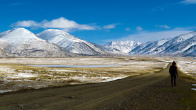 Укомплектуйте личным составом идти на дорогу среди снежных гор Стоковая Фотография RF
