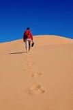 Укомплектуйте личным составом идти на песчанные дюны к небу Стоковое фото RF